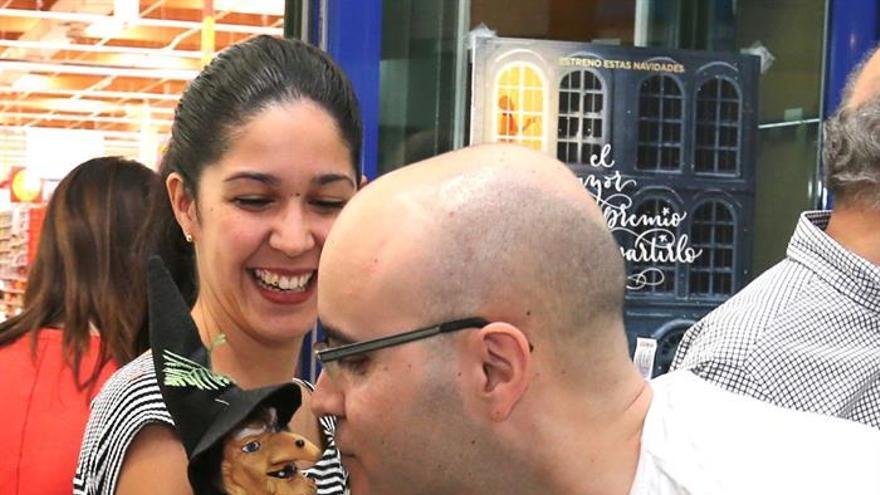 """l gerente de la Administración de Lotería número 8 de Telde """"La Brujita"""", Alberto Suárez, da un beso a la muñeca de la brujita que habitualmente preside su establecimiento"""
