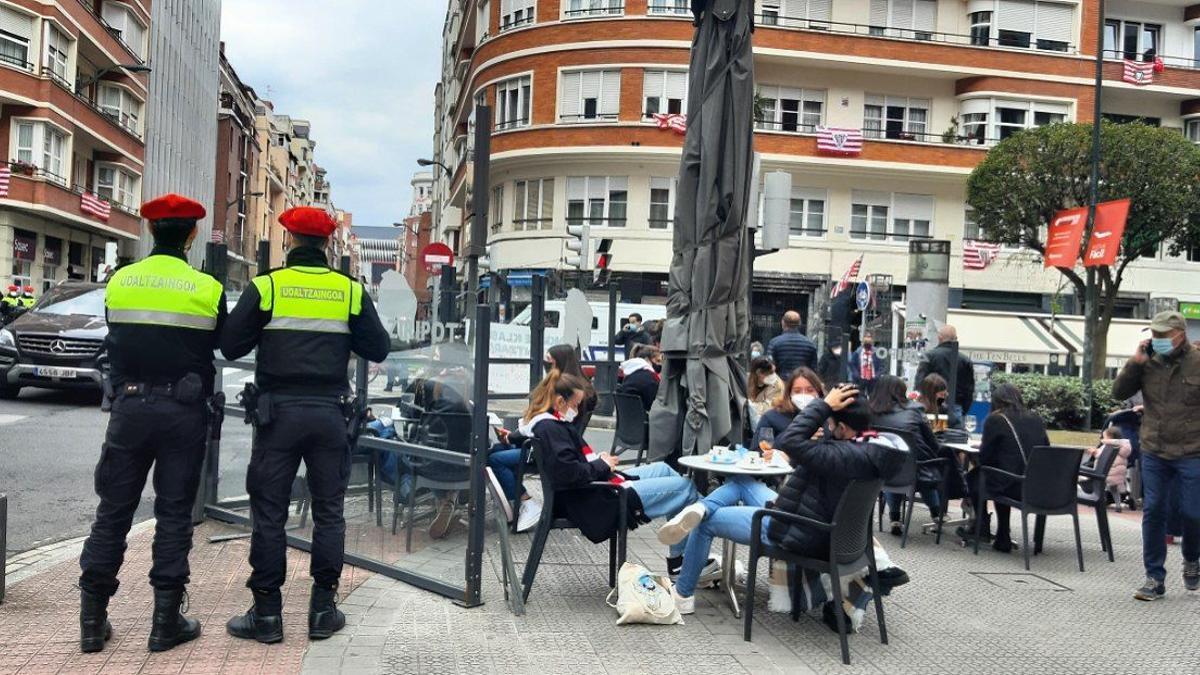 Dos agentes de la policía municipal junto a una terraza en la calle Poza este sábado en Bilbao