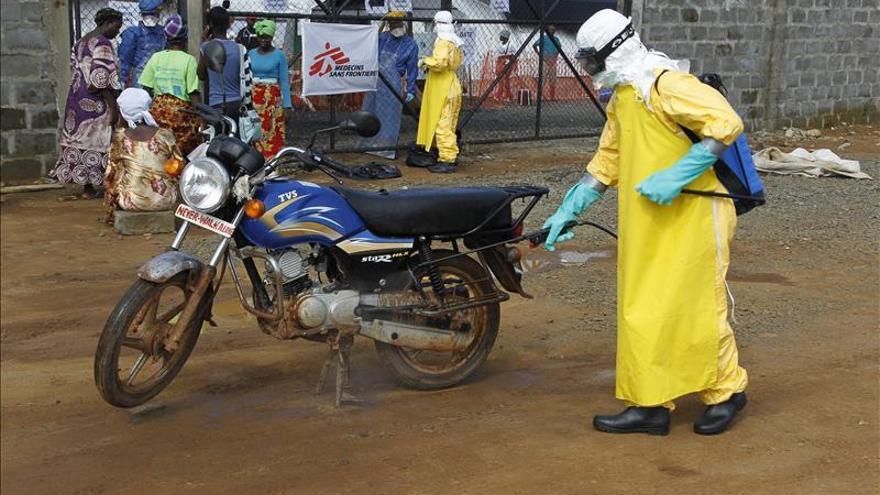 Una enfermera desinfecta una moto cerca de un hospital en Liberia/ Efe