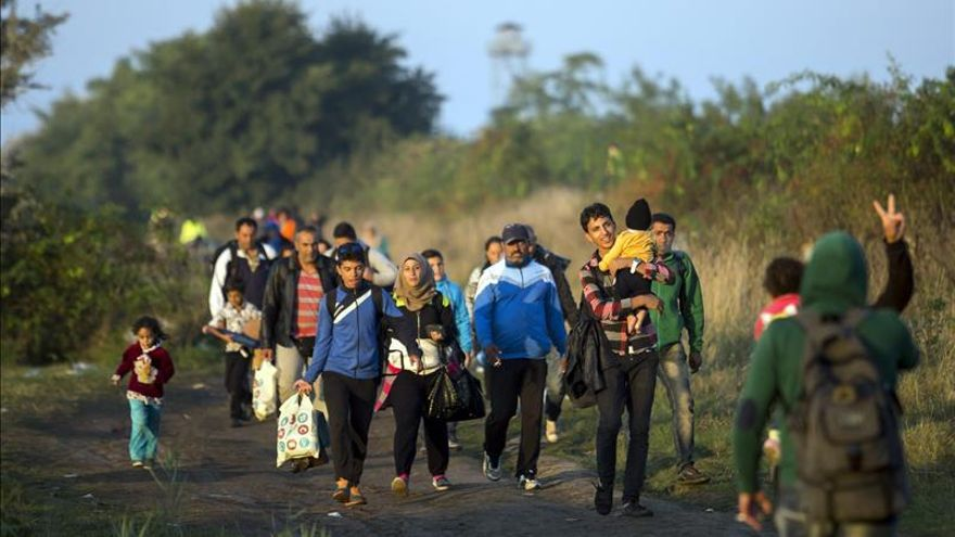 Refugiados caminan por las vías del tren de Horgos a Szeged cerca de Rozke en Hungría este lunes. / Efe.