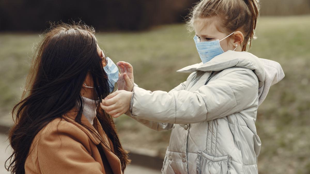 Una madre con su hija usando mascarilla.