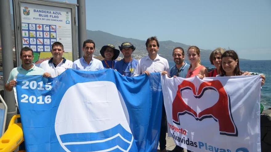 En la imagen, autoridades locales, representantes de empresarios y socorristas, en Los Cancajos, con las banderas Azul y Proyecto Salvavidas Playa.