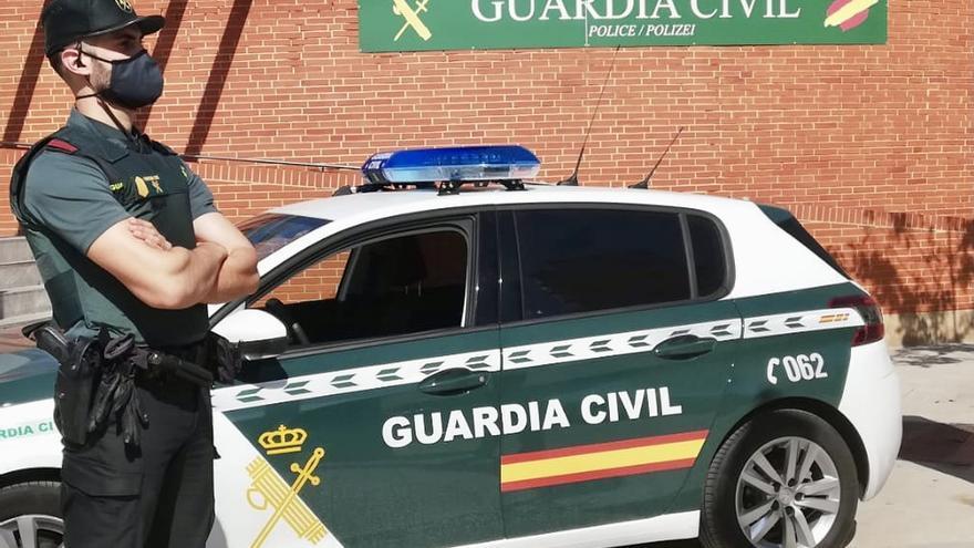 Archivo - Un agente de la Guardia Civil, junto a un vehículo del cuerpo.