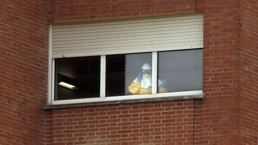 Un sanitario del hospital Carlos III asomado a la ventana de la habitación de Teresa Romero.