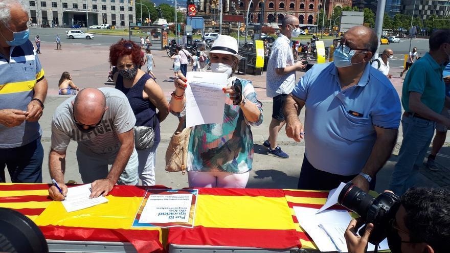 Algunas personas firman contra los indultos en la mesa instalada por el PP en la plaza Espanya de Barcelona.