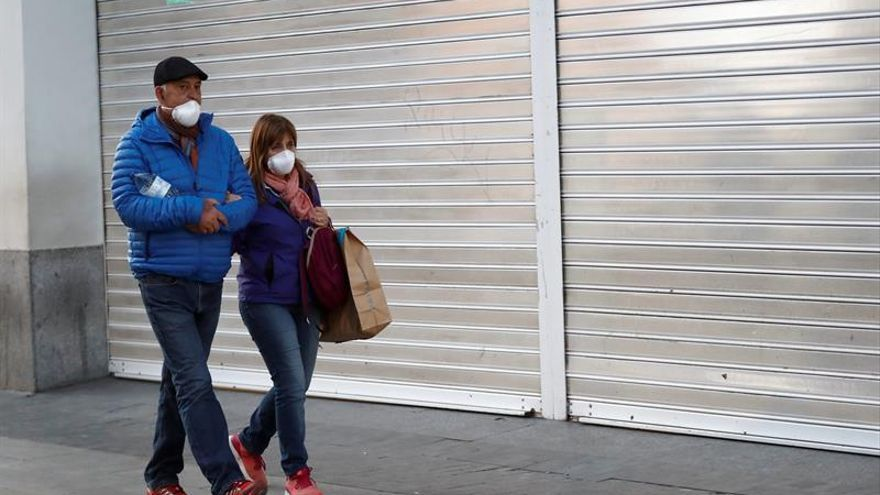 Dos personas caminan por la Gran Vía de Madrid, con comercios cerrados, el pasado viernes.