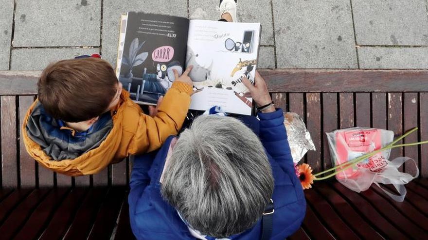 Un niño escucha a su abuela en la lectura de un libro adquirido en una librería.