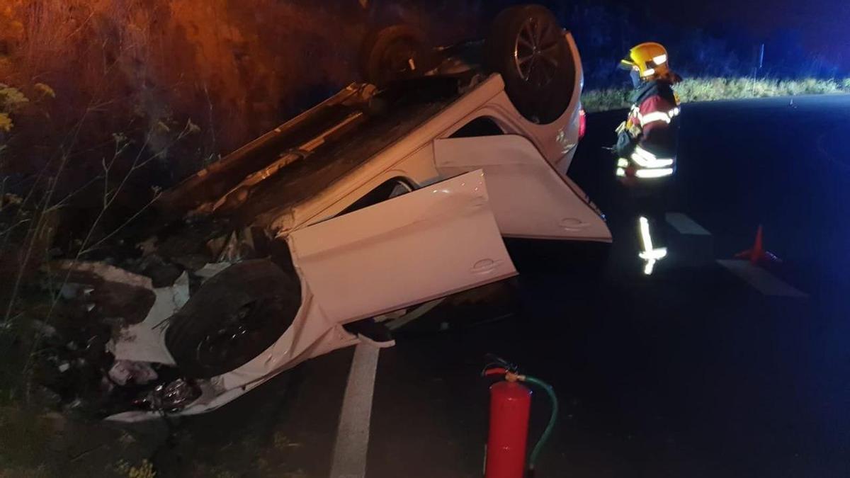 En la  imagen, un bombero junto al vehículo accidentado.