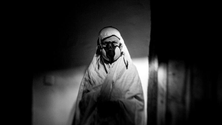 Una mujer utiliza una máscara con un filtro de carbón activado para evitar la inhalación de productos químicos.