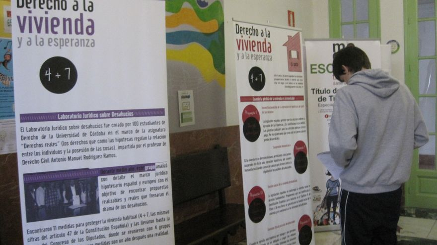 Un estudiante trabaja sobre paneles informativos acerca de los desahucios.