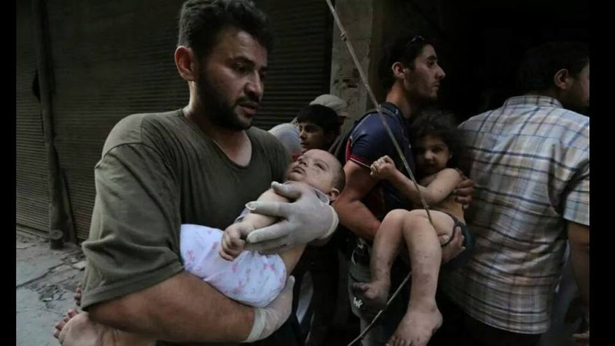 Alaa rescatando niños tras un bombardeo.