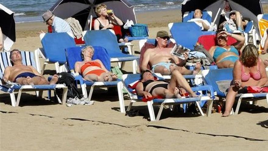 Turistas toman el sol en una playa de Canarias