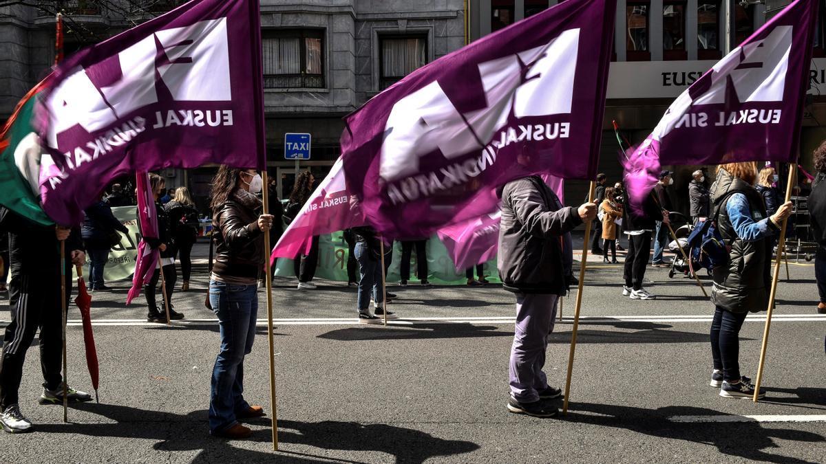 Tres afiliados al sindicato ELA sostienen sus banderas durante la manifestación que ha recorrido las calles de Bilbao este sábado con motivo del Dia del Trabajador.