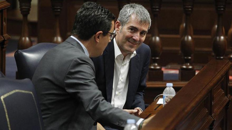 El presidente del Gobierno de Canarias, Fernando Clavijo (d), conversa con el vicepresidente Pablo Rodríguez (i), durante la sesión plenaria del Parlamento regional.