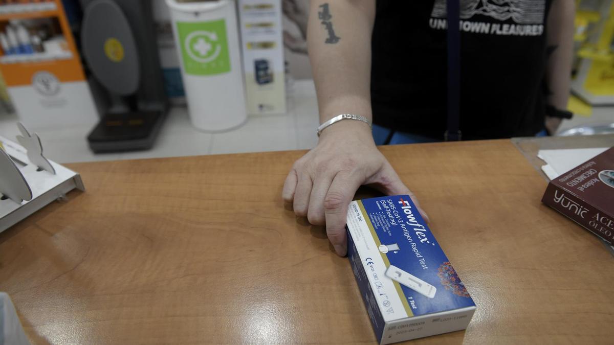 Un cliente enseña un test de antígenos de detección del COVID-19 en una farmacia