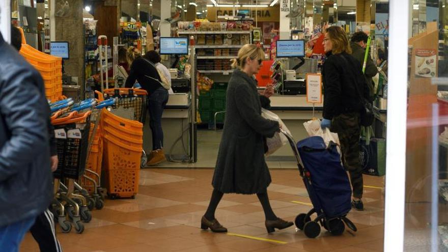Varias personas realizan sus compras en un supermercado de Torrelavega, (Cantabria).