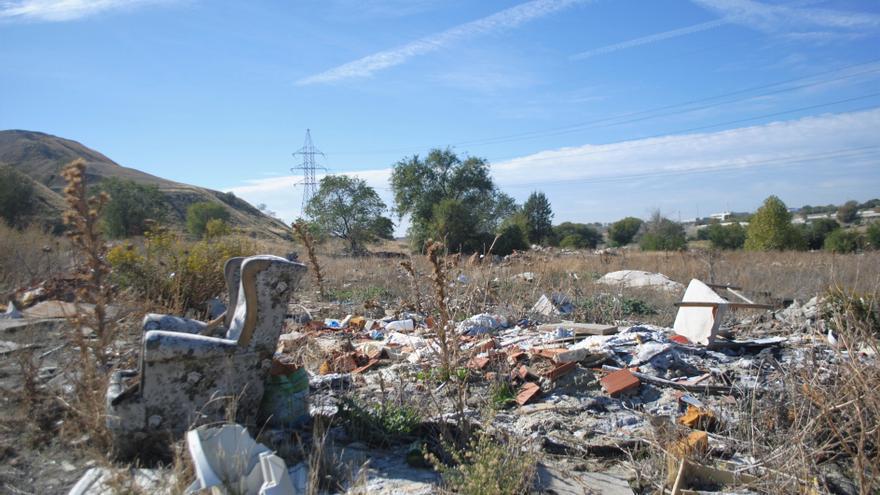 Escombros y un sillón al costado del Camino de la Magdalena, en el Ensanche de Vallecas (Madrid)