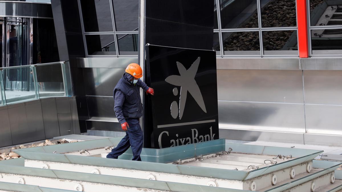 Operarios sustituyen uno de los rótulos de Bankia por otro de la nueva CaixaBank en las torres Kio de Madrid. EFE/ Zipi/Archivo