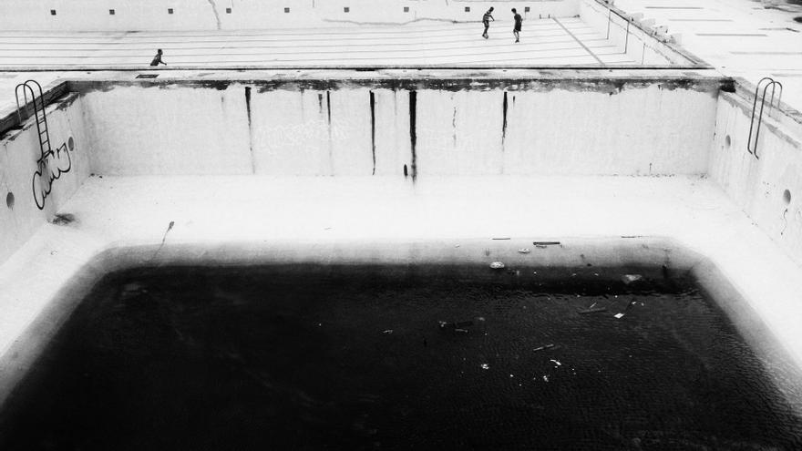 En una isla rodeada de agua, alguien aguarda en una piscina que no la tiene. ¿Hay mayor evidencia de la tensión entre la fachada pública y la vida privada, entre el discurso altisonante y la realidad precaria, entre la esperanza y la espera?