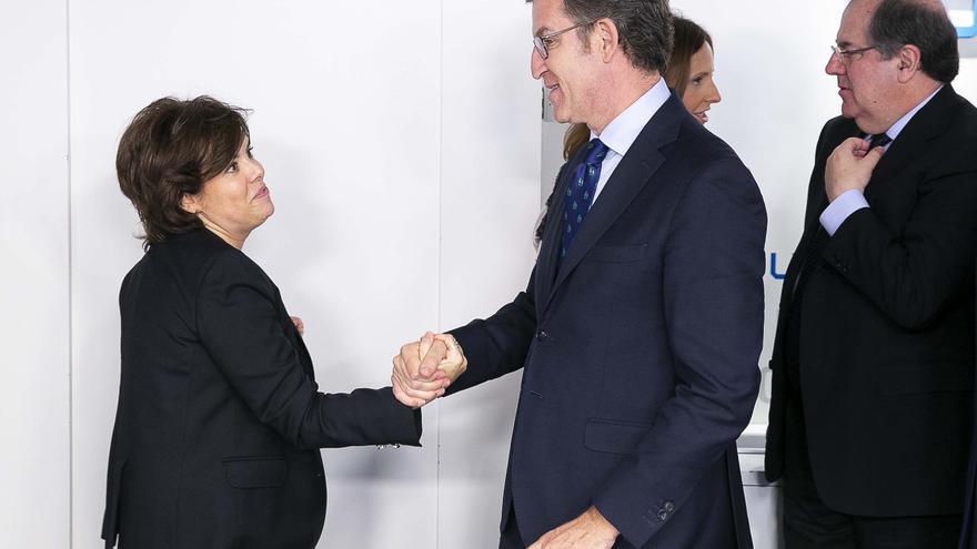 Sáenz de Santamaría y Feijóo se saludan antes de escuchar el anuncio de dimisión de Rajoy