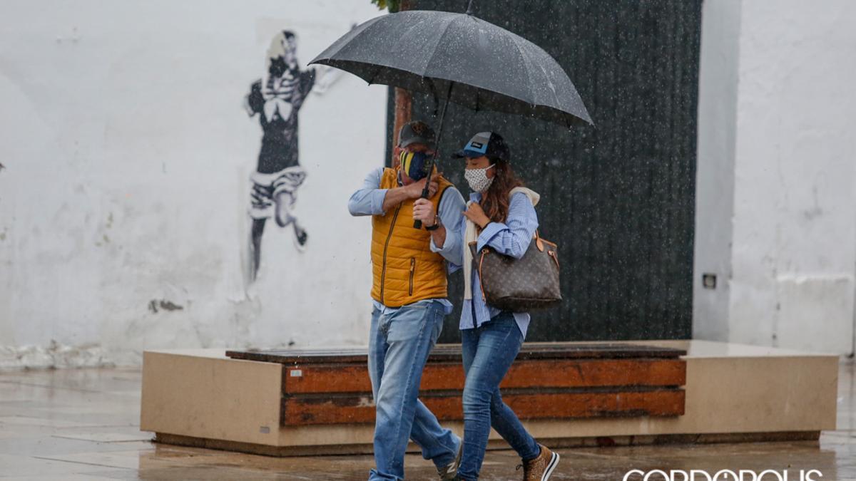 Unos cordobeses se protegen de la lluvia
