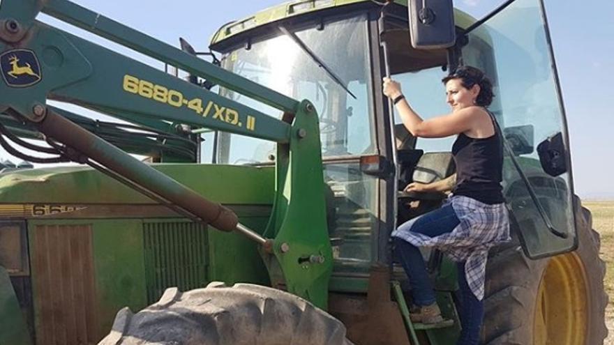 Una agricultora sube a su tractor.