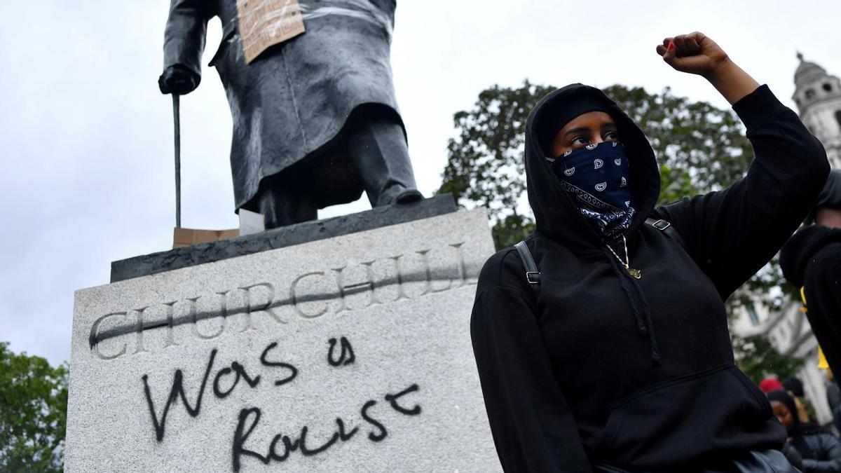 Un manifestante frente a un graffiti en una estatua de Winston Churchill en Londres durante una protesta de 'Black Lives Matter ' en 2020