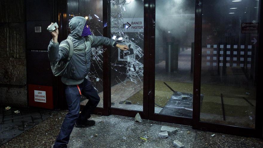 Un joven acaba a pedradas con los cristales de un banco en Colón durante las protestas del 22M / Olmo Calvo