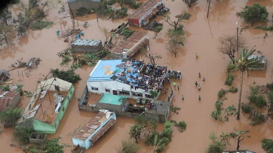 Varias decenas de supervivientes se encaraman a los tejados para evitar el agua.
