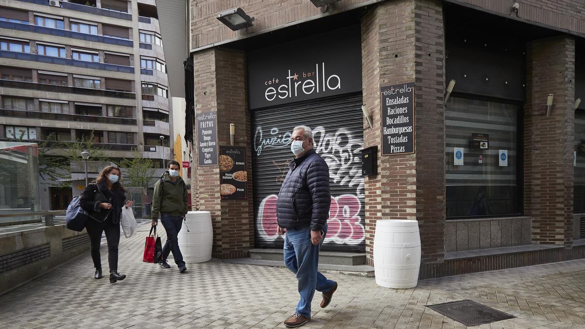 Transeúntes pasean por una calle de Pamplona protegidos con mascarilla debido a la crisis sanitaria de la COVID-19, en Pamplona
