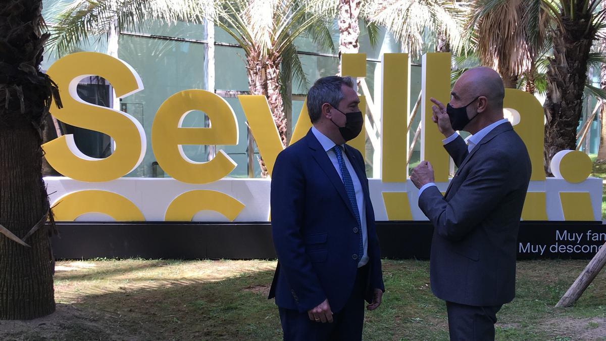Juan Espadas y Antonio Muñoz conversan ante la reproducción del nuevo logo de la ciudad.