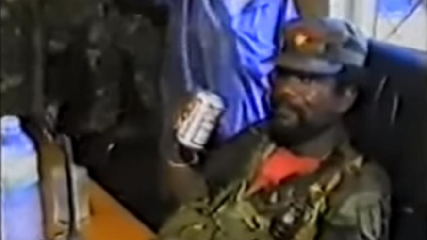 Prince Johnson bebiendo cerveza mientras sus soldados le cortan la oreja al presidente Samuel Doe en 1990.