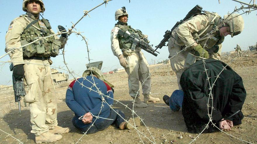Soldados norteamericanos colocan una capucha a dos detenidos en Samarra, Irak, en septiembre de 2003. Foto: Shawn Baldwin/EPA