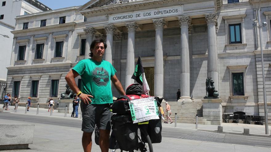 Néstor, el activista que ha recorrido España en bicicleta, a la puerta del Congreso / Foto: Marta Jara