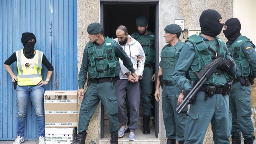 El presunto yihadista detenido en el aeropuerto de Adolfo Suárez Madrid-Barajas, es trasladado por agentes de la Guardia Civil tras el registro a su vivienda en el número 16 de la calle Tinajo, en la localidad de Vecindario, en la isla de Gran Canaria. EFE/Quique Curbelo