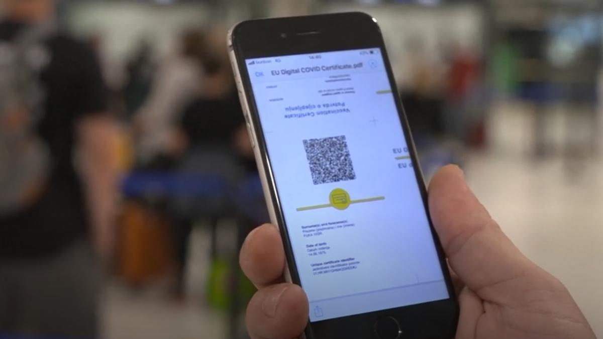Un viajero muestra su pasaporte Covid en el móvil antes de coger un avión en Barajas.