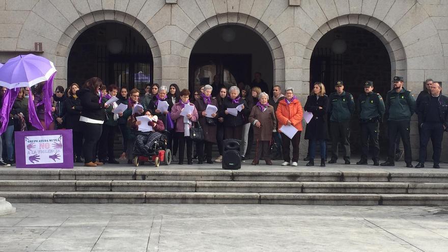 La concejala de Igualdad de Vox en El Espinar (con abrigo negro junto a un agente) en la lectura del manifiesto contra la violencia machista.