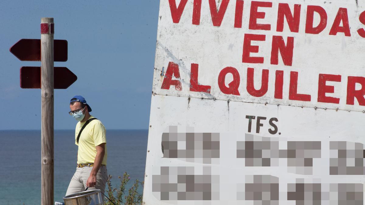 Un hombre camina junto a un cartel de viviendas en alquiler