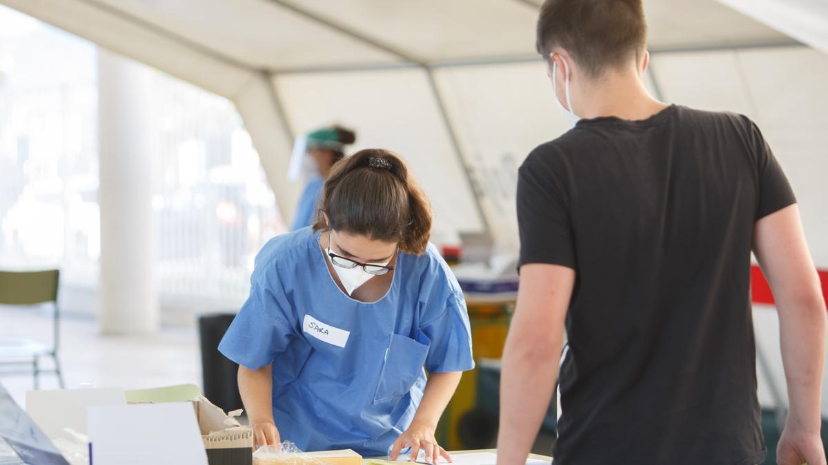 Una enfermera toma los datos de un joven del barrio pamplonés de Mendillorri que ha acudido a hacerse una prueba PCR