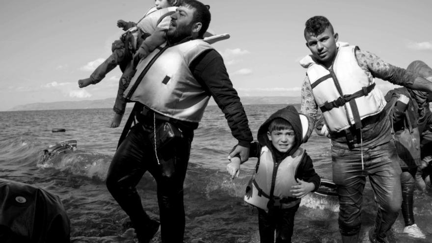 Un padre con sus hijos sale del mar tras cruzar de Turquía a Lesbos / Juan Carlos Mohr