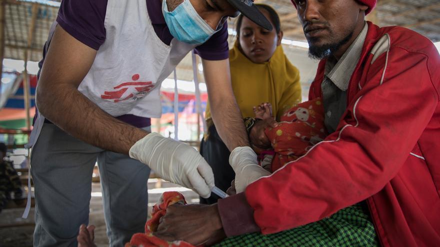 Boshir Ullah, un refugiado rohingya de 25 años, acaba de llegar de Myanmar junto con su esposa, su madre y sus tres hijos. En la foto, Ferungada, su hijo menor, está siendo inmunizado por un equipo de MSF en el punto de entrada de Sabrang. Foto: Anna Surinyach/MSF