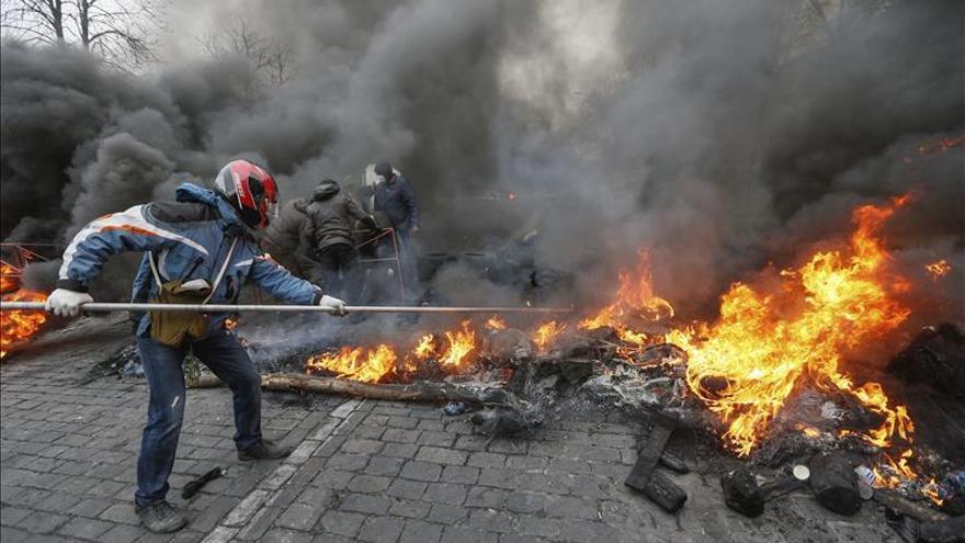 Los manifestantes prenden fuego a una barricada durante los disturbios.