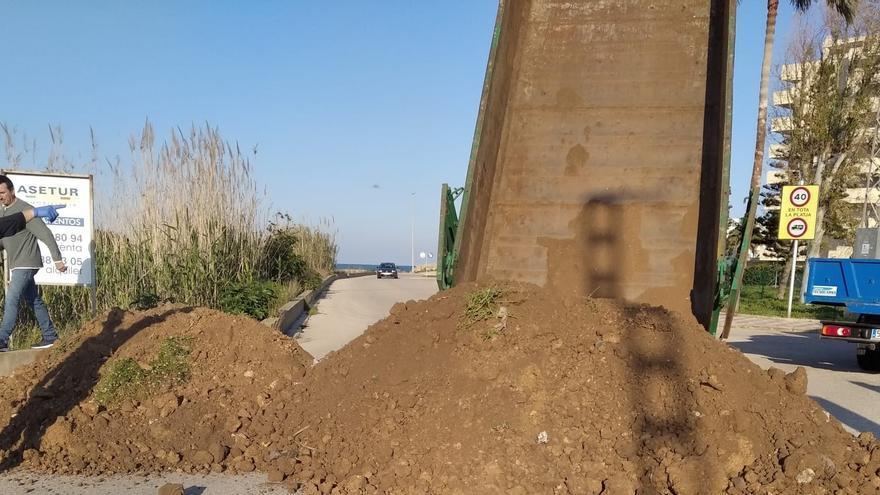 Un camión vuelca tierra para hacer una barricada e impedir el acceso a la playa
