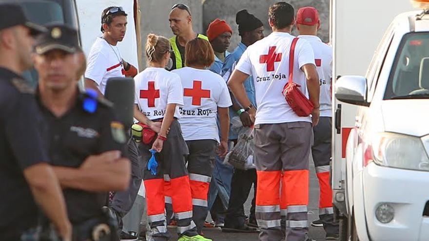 Los inmigrantes llegados en la patera a Arguineguín son atendidos por miembros de Cruz Roja. (Foto: Alejandro Ramos).