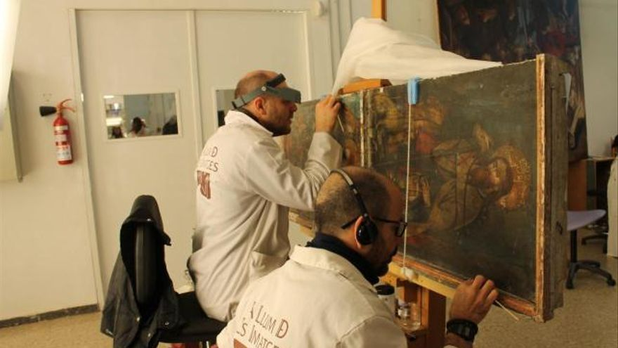 Técnicos de la Luz de las Imágenes restaurando un retablo religioso.