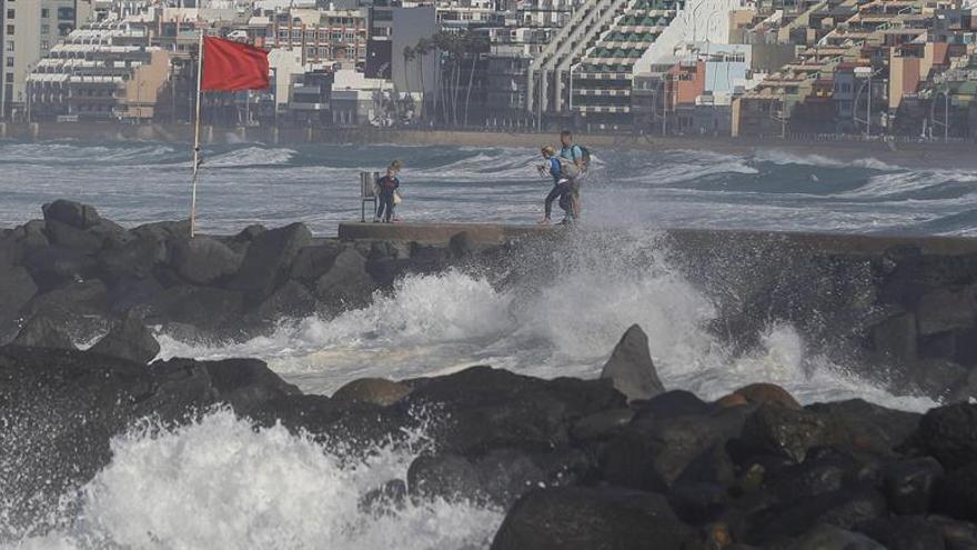 Varias personas se toman fotografías en el paseo de la playa de Las Canteras en Las Palmas de Gran Canaria con el oleaje de fondo. EFE/Elvira Urquijo A.