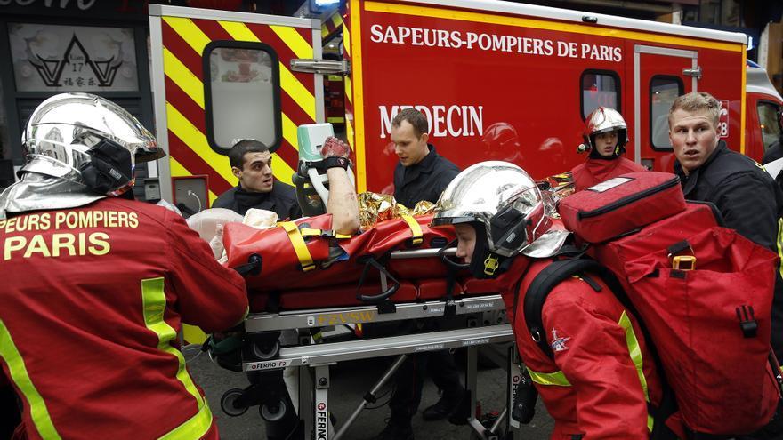 Bomberos y médicos llevan a una persona herida de la escena de una explosión en una panadería cerca de la Rue de Trevise en París, Francia