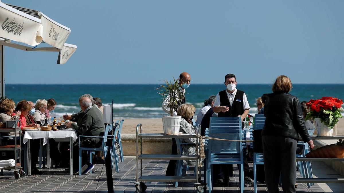 Un camarero informa a una mujer de que no dispone de mesas al tener reservadas todas sus mesas tanto en la terraza como el comedor, en uno de los restaurantes de la playa de la playa de la Malvarrosa de Valéncia. EFE/Manuel Bruque/Archivo