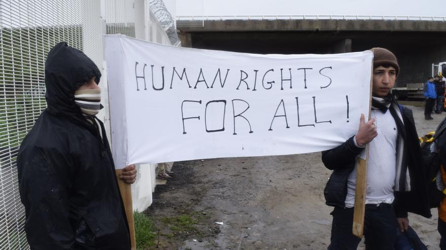 """""""Derechos humanos para todos"""", reza la pancarta que portan dos refugiados en el campamento de Calais / Eduardo Granados"""