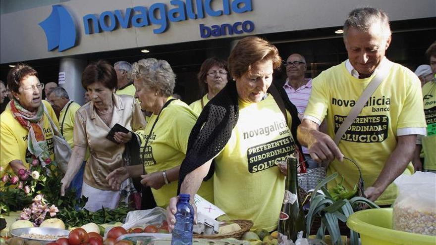 Afectados por las participaciones preferentes delante de la sede central de Novagalicia Banco en Vigo. / Efe